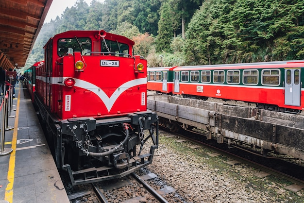 Red train on alishan forest railway stop on the platform.