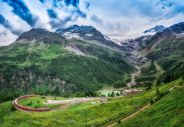 Red train bernina express to the passage in the mountains.