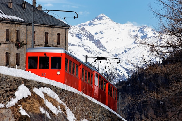 Red train in french alpine mountain in winter