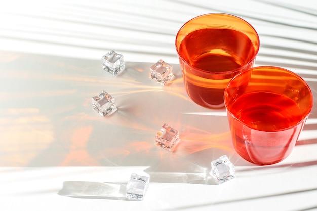 Красные и прозрачные очки, кусочки льда на белом фоне