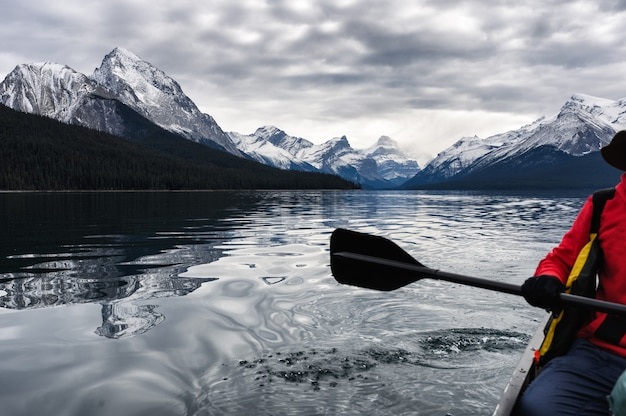 Red traveler canoeing and rocky mountain in maligne lake