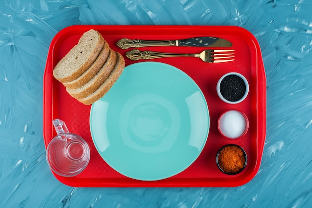 A red tray of an empty blue plate with sliced brown bread and spices .