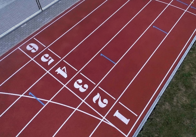 Red treadmill at the stadium with the numbering from one to eight.