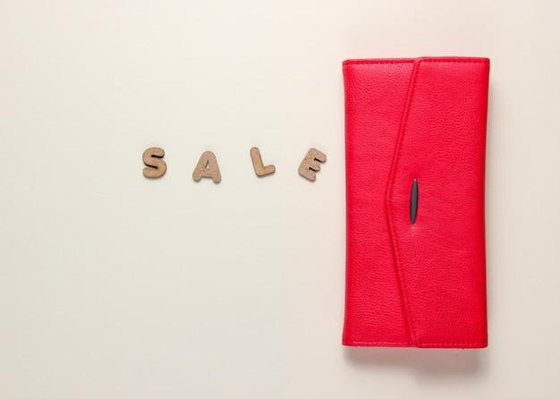 テキスト販売のベージュの表面に赤いトレンディな財布。