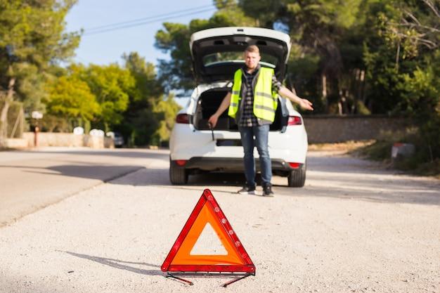 Человек в красном треугольнике не знает, что случилось с машиной