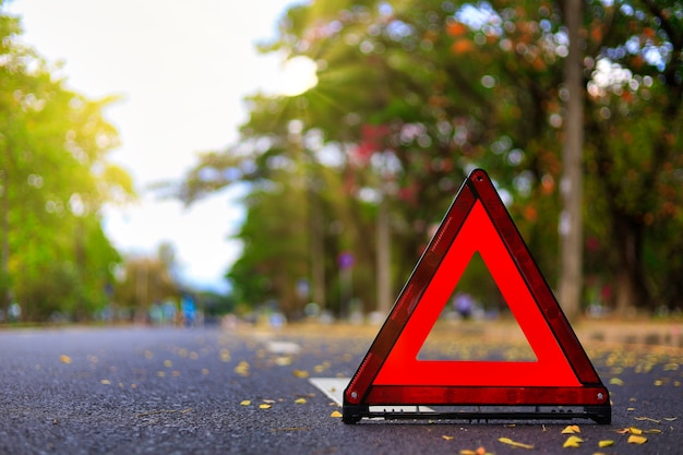 Red triangle, red emergency stop sign, red emergency symbol on road.