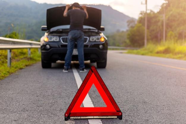 警告のための道路上の赤い三角形の標識には、故障した車のボンネットと車を修理する人がいる車があります。