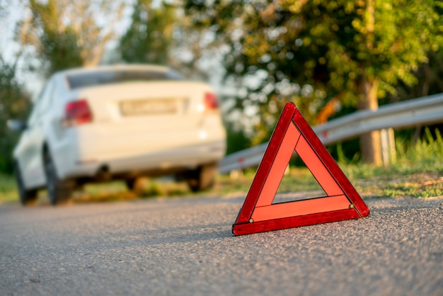 A red triangle sign on the road as the symbol of the car crash accident on highway