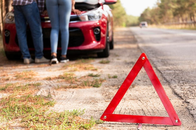 Red triangle sign on the road for car problems while traveling