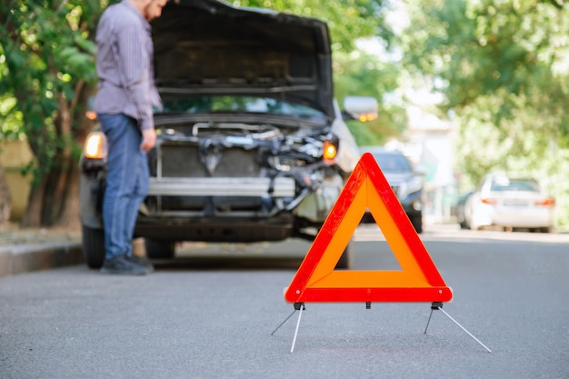 Red triangle warning sign of car accident on road. triangle in front of wrecked car and driver man. injured person man in accident looks under the hood of wrecked car after an accident.