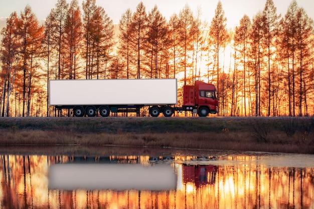 Красный грузовик на дороге на закате. сосредоточьтесь на контейнере