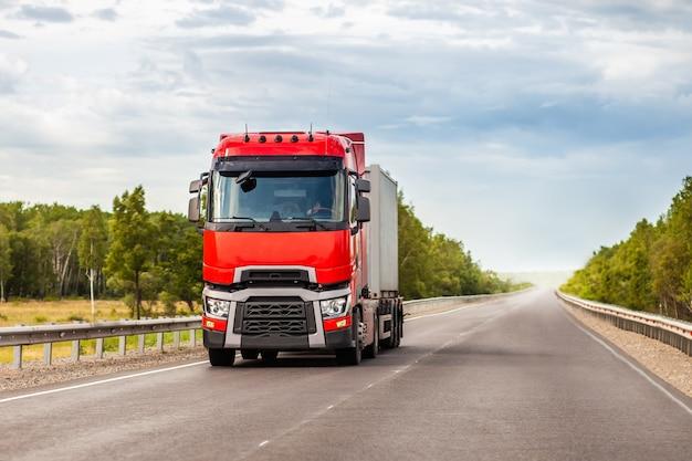 Красный грузовик на дороге летом