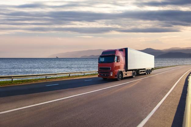 바다 근처 도로에 빨간 트럭