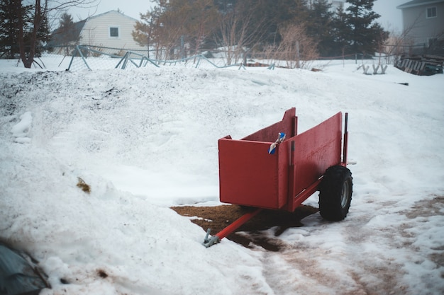 Red truck on snow covered ground during daytime