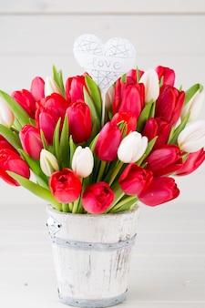 白い木製の背景に赤いチューリップの花束