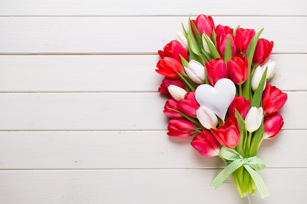 Букет красных тюльпанов на белом деревянном