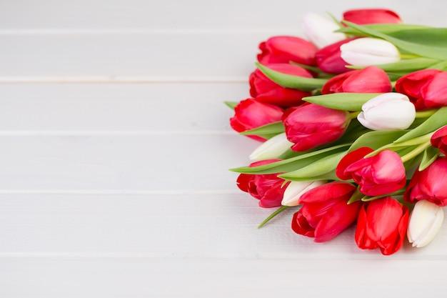白い木の上の赤いチューリップの花束