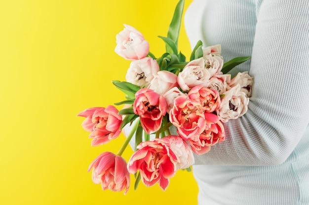 黄色の背景に赤いチューリップの花束。イースターと春のグリーティングカード女性の日のコンセプトテキスト用のコピースペース。