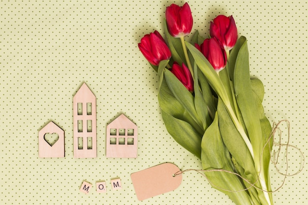Red tulip flower; house models; price tag; and mom word alphabet over yellow backdrop