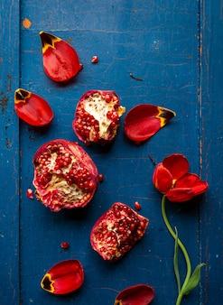赤いチューリップ、暗い青色の背景に種子とザクロ