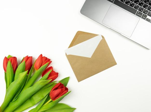 빨간 튤립과 갈색 봉투에 빈 편지는 흰색 테이블에 놓여 있습니다. 목업