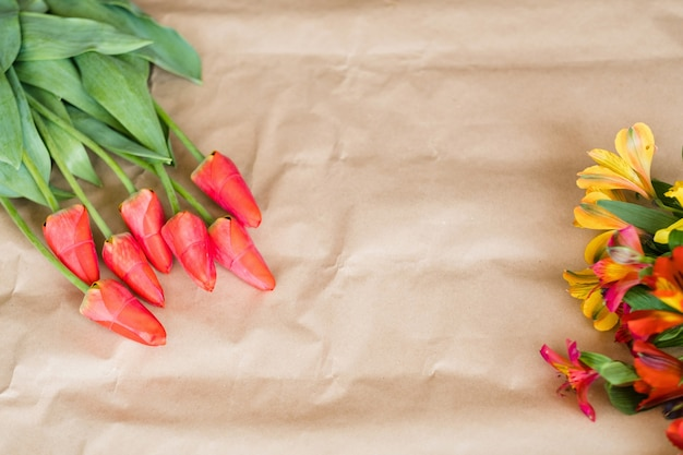 Красные тюльпаны и альстромерии. весенние цветы на фоне крафт-бумаги. природа, флора, травы, красота и концепция праздничного букета.