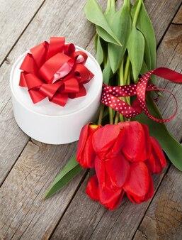Красные тюльпаны и подарочная коробка на день святого валентина над деревянным столом