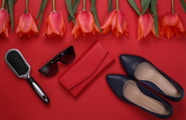 Красные тюльпаны и женские аксессуары на красном фоне. праздник день матери или 8 марта, день рождения. вид сверху