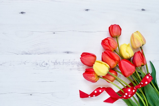 Red tulips bouquet decorated with ribbon on white wooden.