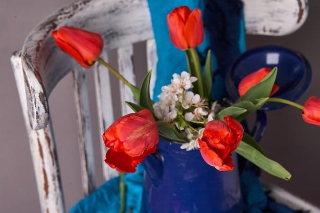 ヴィンテージシェールに青い花瓶の赤いチューリップの花束。バレンタインデー、母の日、誕生日のコンセプト。