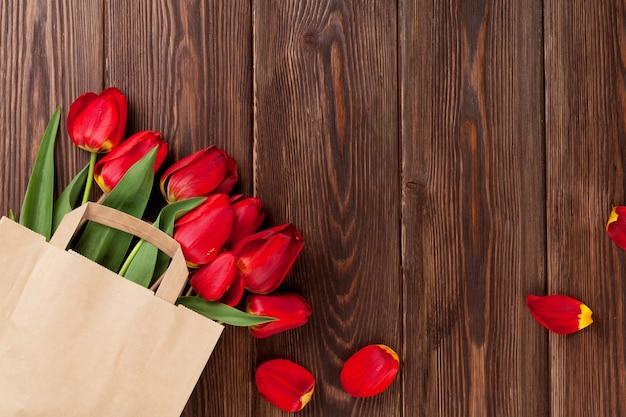 Букет красных тюльпанов в бумажном пакете на фоне деревянного стола с копией пространства