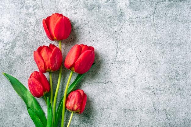 Букет красных тюльпанов на бетонном фоне