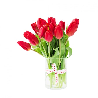 Red tulips bouquet in vase decorated with ribbon.