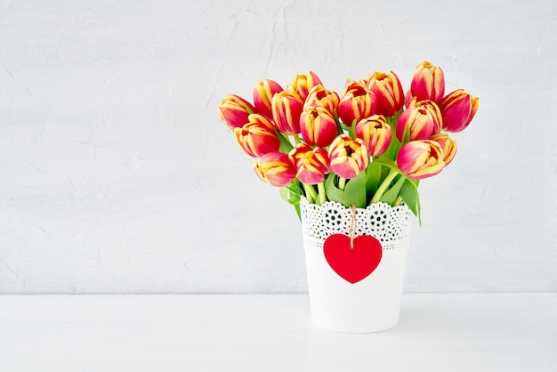 Red tulips bouquet in white vase decorated with red wooden heart. valentines day concept.
