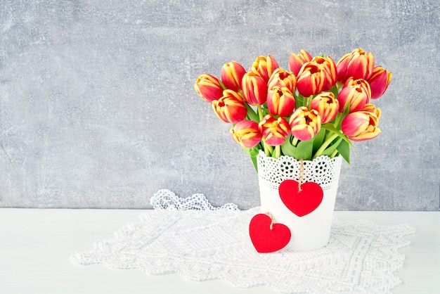Red tulips bouquet in white vase decorated with two red wooden hearts. valentines day concept.