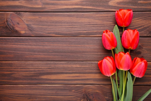 Red tulips on a brown wooden background