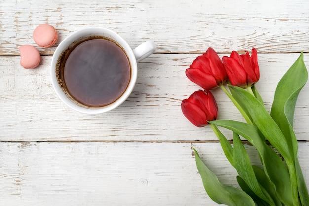 赤いチューリップ、白い木のテーブルの上のコーヒーカップ