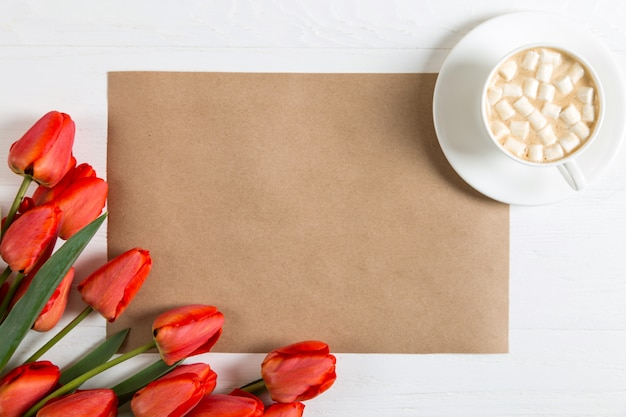 Red tulips, cup of coffee with marshmallows and craft paper template on the blue, blank for a postcard for the teacher's day. copy space.