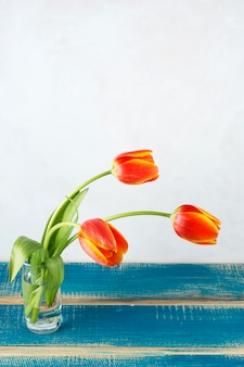 Red tulips in glass vase on wooden table