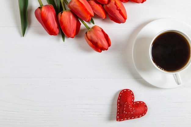 Red tulips, heart and a cup of coffee on the white table. morning gift for spring holiday, mother's day. copy space.