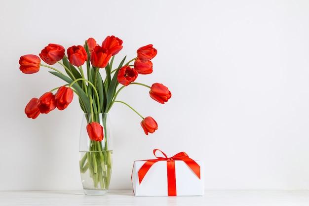 Красные тюльпаны в вазе и подарок на столе на белом.