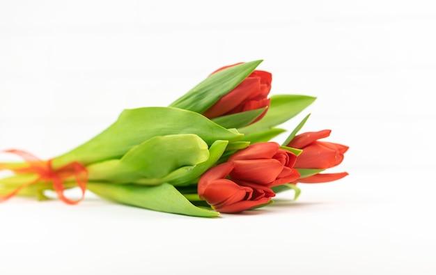 Красные тюльпаны лежат на белом столе
