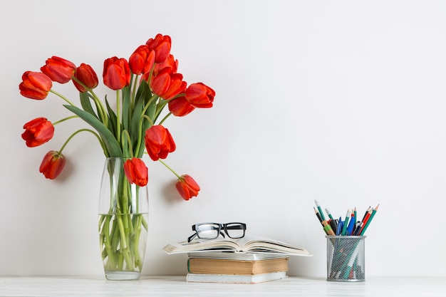 Red tulips in a vase, books and school supplies on white.