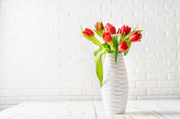 Red tulips in a white vase against the white background