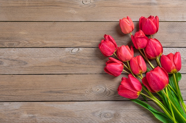 Red tulips on wooden background with space for text, message.