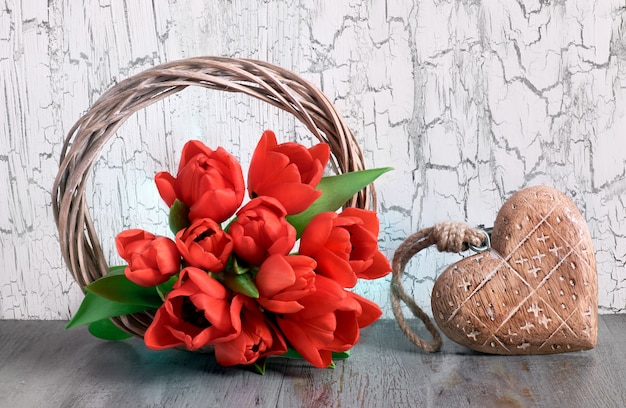 Red tulips and wooden heart on white cracked background