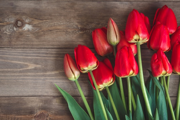 Red tulips on wooden table, top view
