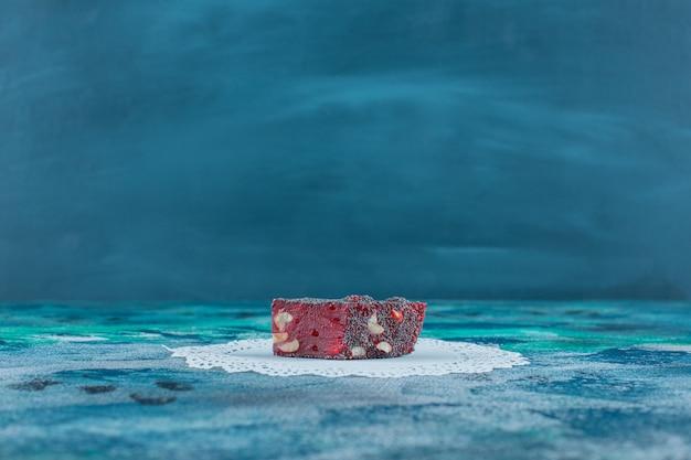 大理石のテーブルの上にあるコースターで赤いターキッシュロクムをお楽しみください。