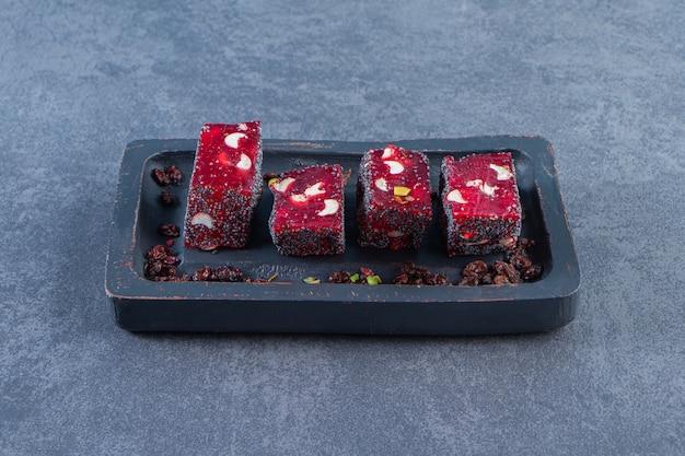 Delizie turche rosse in un piatto di legno, sulla superficie di marmo