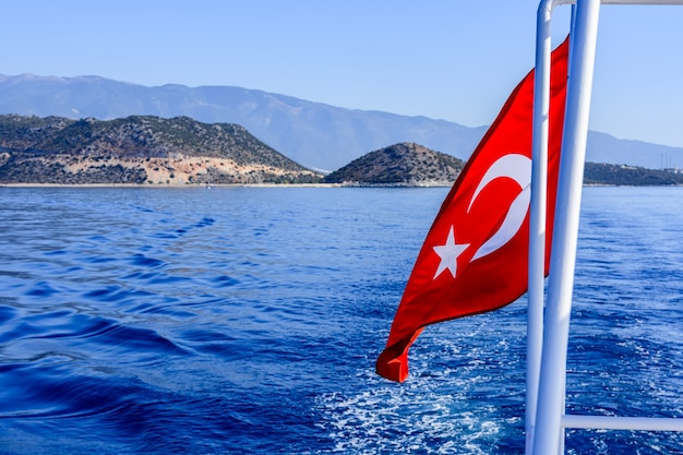 Red turkish flag waving over the mediterranean sea